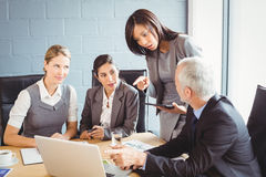Businesspeople interacting in conference room Royalty Free Stock Photo