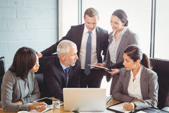 Businesspeople interacting in conference room Stock Photo