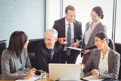 Businesspeople interacting in conference room Stock Images