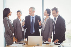 Businesspeople interacting in conference room Stock Image