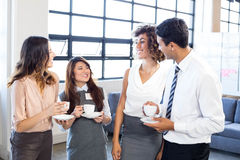 Businesspeople interacting in office during breaktime Royalty Free Stock Photos