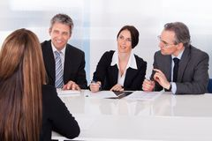 Businesspeople interviewing woman Royalty Free Stock Image