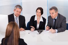 Businesspeople interviewing woman. Group Of Businesspeople Interviewing Woman In Office stock photo