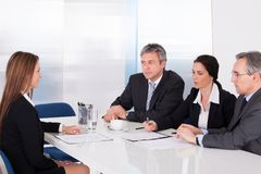 Businesspeople interviewing woman Royalty Free Stock Photo