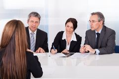 Businesspeople interviewing woman Stock Images