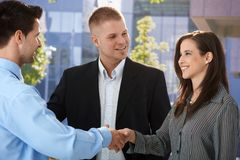 Businesspeople introducing outside of office. Shaking hand, smiling stock images