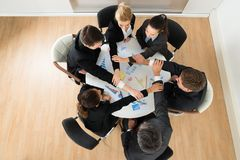Businesspeople joining hands. High Angle View Businesspeople Team Joining Hands In Office royalty free stock photography