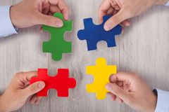 Businesspeople joining multicolored puzzle pieces at desk Royalty Free Stock Photos