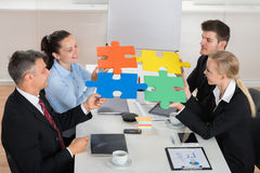 Businesspeople Joining Puzzle Piece. Happy Businesspeople Joining Multicolored Puzzle Piece In Meeting stock image