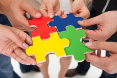 Businesspeople joining puzzle pieces. Cropped image of businesspeople joining puzzle pieces in office stock images