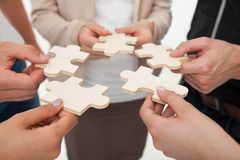 Businesspeople joining puzzle pieces. Cropped image of businesspeople joining puzzle pieces in office stock image