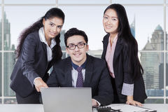 Businesspeople with laptop smiling on the camera. Group of multi ethnic businesspeople discussing with laptop in office and smiling on the camera Royalty Free Stock Photos