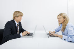 Businesspeople with laptops looking at each other in office Royalty Free Stock Image