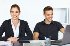 Businesspeople laughing in office. Two young cheerful businesspeople sitting at table in office and laughing Stock Image