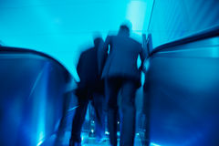 Businesspeople Leaving an Office Building, Motion Blur. Two businesspeople on escalator in motion Royalty Free Stock Photo