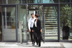 Businesspeople leaving office. Businesspeople interacting with each other while leaving office royalty free stock image