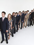 Businesspeople In Line Leaning Over Stock Photo