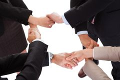 Businesspeople linking hands - teamwork. Cropped overhead view of a diverse group of businesspeople linking hands in a team stock photography