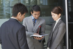 Businesspeople Looking At Book Outdoors Stock Images