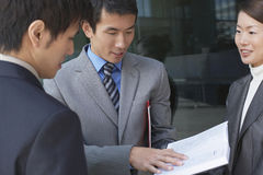 Businesspeople Looking At Book Outdoors Stock Image