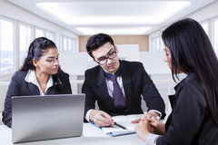 Businesspeople looking at employment contract. Three young businesspeople looking at employment contract with laptop on the table, shot in the office Royalty Free Stock Photos