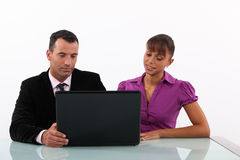 Businesspeople looking at a laptop Stock Images