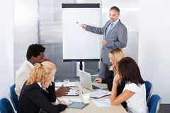 Businesspeople looking at man explaining. Businesspeople Looking At Businessman Explaining In Presentation royalty free stock photos
