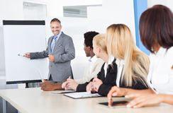 Businesspeople looking at man explaining. Businesspeople Looking At Businessman Explaining In Presentation stock photography