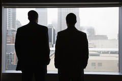 Businesspeople Looking Out of a Window. Rear view of two businessmen as they stare out a large window with a city view. They have their hands in their pockets royalty free stock image