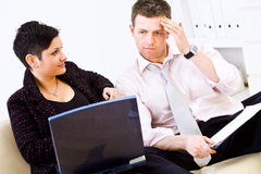 Businesspeople looking troubled. Businessman and businesswoman working together, sitting of sofa, holding laptop and looking troubled Stock Image