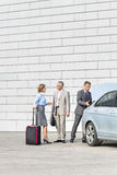 Businesspeople with luggage communicating outside car on street Royalty Free Stock Photo