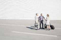 Businesspeople with luggage communicating on street Stock Image