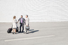 Businesspeople with luggage communicating on street Royalty Free Stock Photo