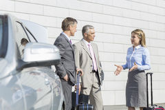 Businesspeople with luggage discussing outside car Royalty Free Stock Photo