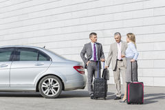 Businesspeople with luggage discussing outside car on street Royalty Free Stock Photos