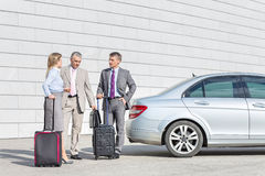 Businesspeople with luggage discussing outside car on street Royalty Free Stock Images