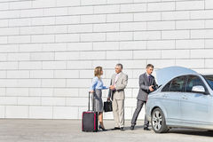 Businesspeople with luggage shaking hands outside car on street Stock Photo
