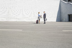 Businesspeople with luggage talking on street Royalty Free Stock Image