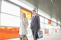 Businesspeople with luggage walking in railroad station Stock Photo