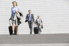 Businesspeople with luggage walking on street Stock Photos