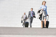 Businesspeople with luggage walking on street royalty free stock photos