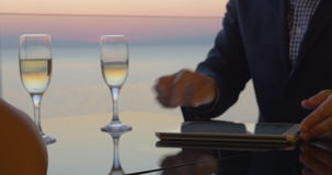 Businesspeople making a deal and drinking wine. Businessman and businesswoman shaking hands, signing the contract on tablet computer and celebrate deal with wine stock video footage