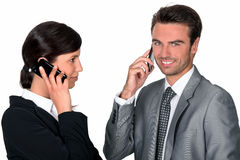 Businesspeople making simultaneous calls Stock Photography