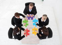 Businesspeople med figursågen lappar sammanträde på tabellen royaltyfri bild