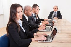 Businesspeople In Meeting. Businesspeople Sitting At Conference Table Using Laptop stock photos