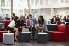 Businesspeople Meeting In Busy Lobby Of Modern Office Stock Images