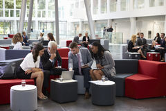 Businesspeople Meeting In Busy Lobby Of Modern Office Royalty Free Stock Photography