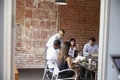 Businesspeople Meeting In Modern Boardroom Through Doorway Stock Photo