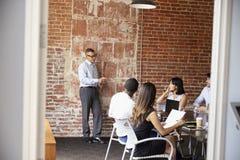 Businesspeople Meeting In Modern Boardroom Through Doorway Stock Photos