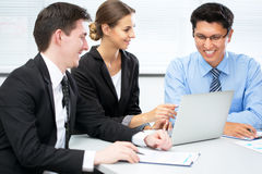 Businesspeople in a meeting at office. Group of happy businesspeople in a meeting at office stock photo